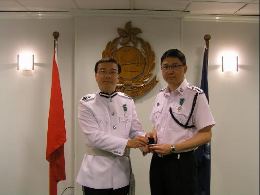 处长(管制)赵伟佳(左)颁发香港入境事务长期服务奖章