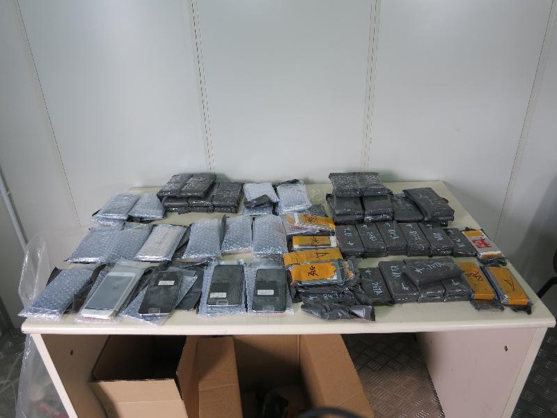 香港海關今日(七月十三日)在落馬洲管制站檢獲一百四十部未列艙單的智能電話。圖示檢獲的懷疑走私智能電話。