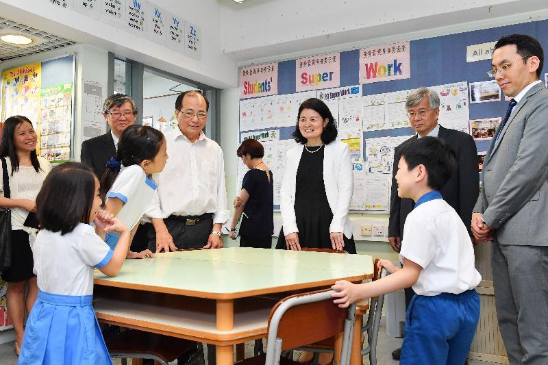 教育局局長吳克儉(左三)今日(七月十八日)參觀沙田崇真學校的英語活動室,並與學生交談。