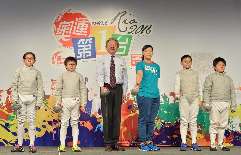 財政司司長曾俊華(左三)今日(七月二十六日)在香港電台奧運節目啟動禮上,與司儀余翠怡(右三)和劍擊運動員以劍擊敬禮為活動揭幕。