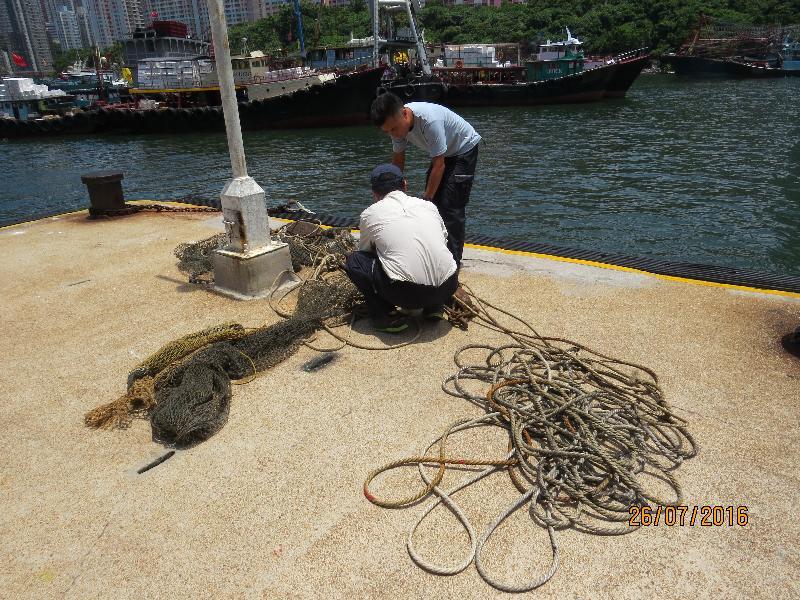 漁農自然護理署(漁護署)人員今日(七月二十六日)進行反非法捕魚行動,在南丫島圓角對開海面截獲一艘涉嫌非法作業的拖網漁船。圖示漁護署人員處理在船上檢走的漁具,包括漁網及繩索。
