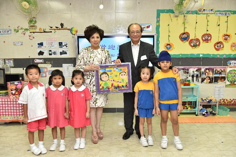 教育局局長吳克儉(後排右)今日(八月二十九日)獲保良局李徐松聲紀念幼稚園的學生致送畫作。