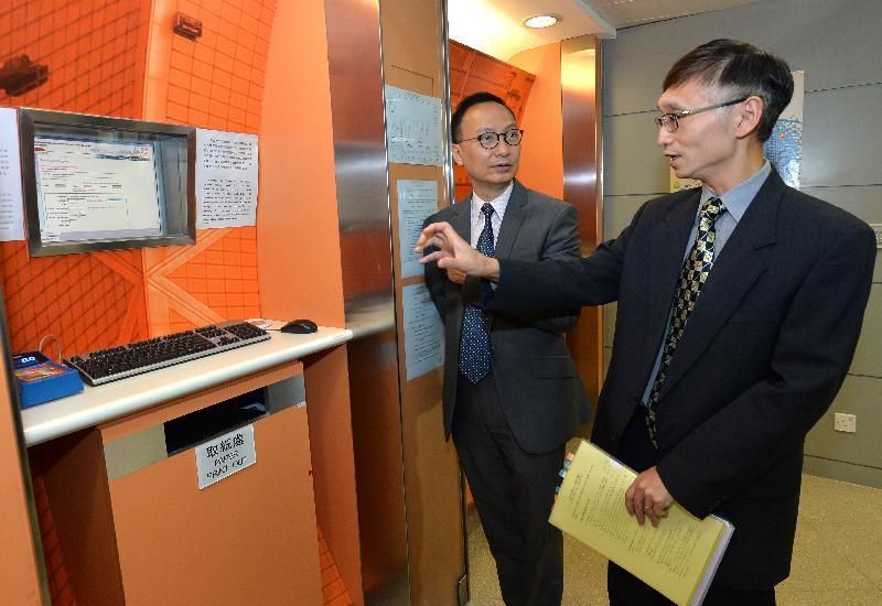 公務員事務局局長張雲正(左)今日(九月二十二日)聽取土地註冊處人員介紹自助查冊終端機。
