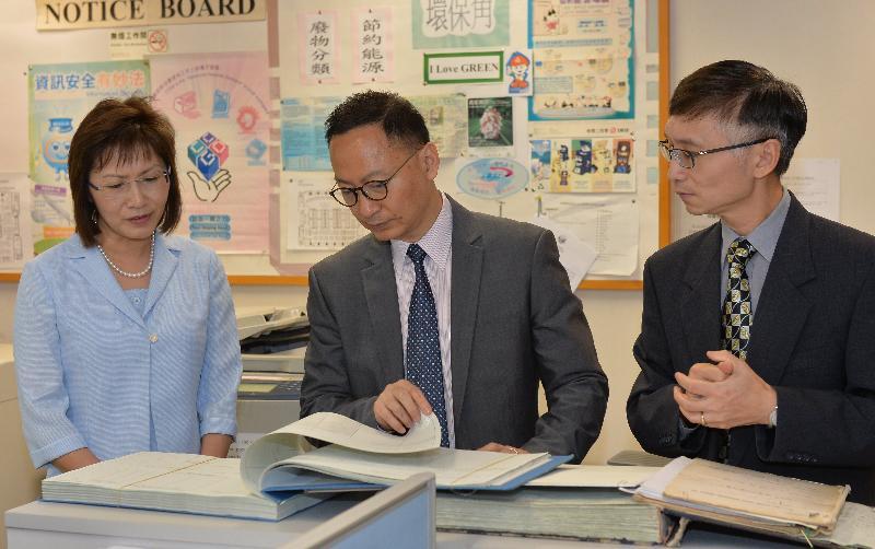 在土地註冊處處長張美珠(左)陪同下,公務員事務局局長張雲正(中)今日(九月二十二日)在土地註冊處聽取人員介紹業主立案法團登記紀錄。
