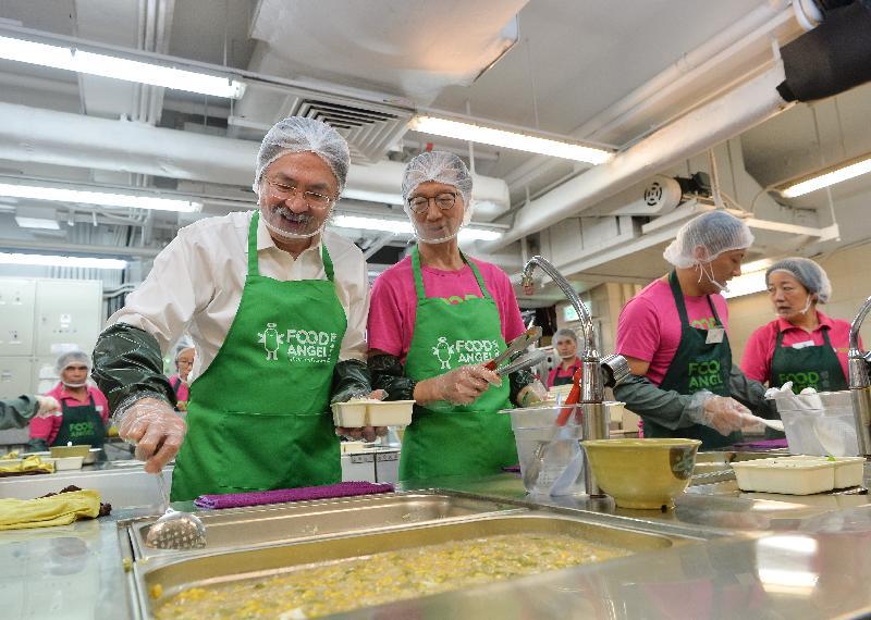 財政司司長曾俊華(左一)和惜食堂主席梁錦松(左二)今日(十月三日)與義工一同為「惜食飯餐感謝宴」準備飯盒。