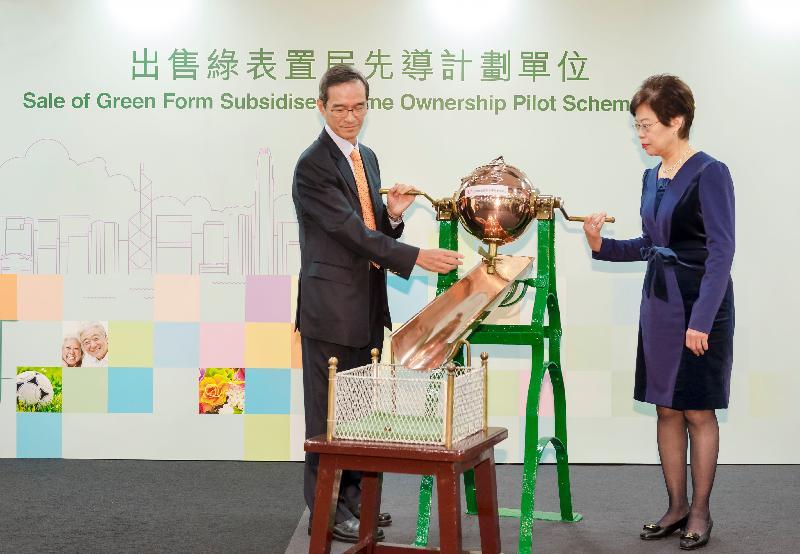 香港房屋委員會資助房屋小組委員會主席黃遠輝(左)今日(十二月八日)在房屋署助理署長(房屋資助)何樂素芬陪同下,主持「出售綠表置居先導計劃單位」的攪珠儀式,以決定詳細審核申請人資格及選樓的次序。