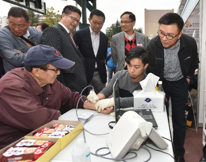 署理財政司司長陳家強(右一)今日(十二月十七日)在萬眾同心千歲宴暨「健樂社區.科技為民」同樂日參觀攤位。
