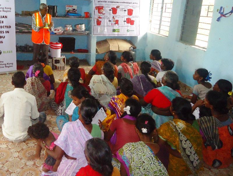 救援機構的當地職員向印度水災災民講解安全使用食水及衞生用品的關注事項。