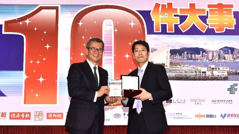 財政司司長陳茂波今日(一月二十三日)出席「2016香港商界最關注的十件大事」評選頒獎典禮。圖示陳茂波(左)頒發頭獎予得獎者。