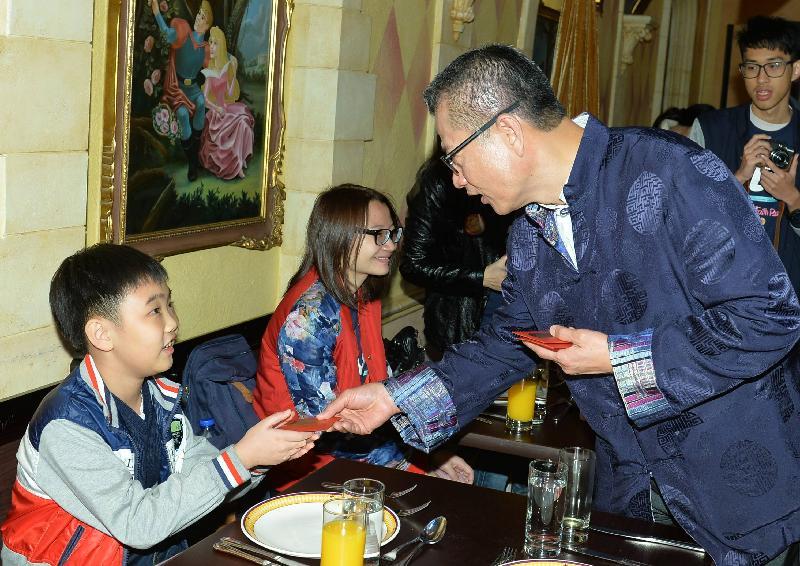 財政司司長陳茂波(右)今日(一月二十八日)出席香港迪士尼樂園「惜食傳福」賀雞年活動,與小朋友一同分享新春的喜悅。