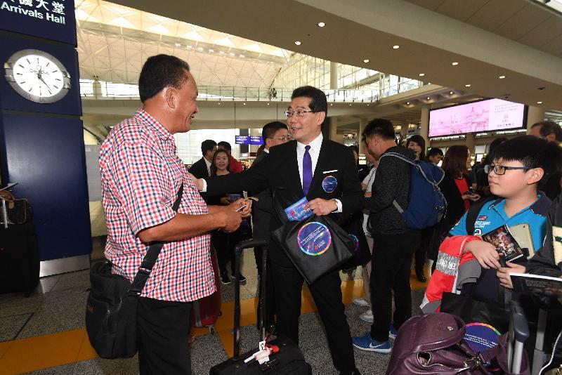 商務及經濟發展局局長蘇錦樑(中)今日(三月三十一日)在香港國際機場向旅客派發「慶祝香港特別行政區成立二十周年禮遇精選」小冊子和紀念品。