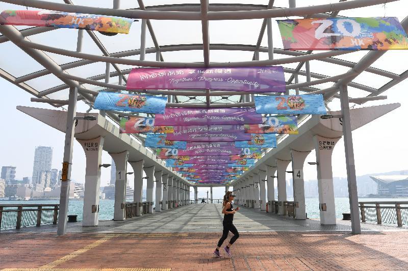 香港的主要街道及中环海滨一带悬挂了灯柱彩旗和横额,庆祝特区成立20周年。图为中环海滨码头的城市景观布置。
