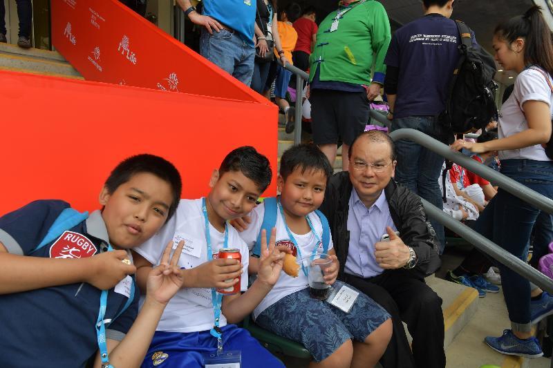 政務司司長暨扶貧委員會主席張建宗今日(四月八日)在香港國際七人欖球賽中主持Mission Possible兒童派對。圖示張建宗(右一)與兒童一起觀賞香港國際七人欖球賽。