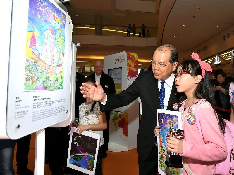 香港特別行政區成立二十周年海報設計比賽一名得奬者今日(四月十四日)向政務司司長張建宗介紹其得奬作品。