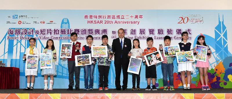 政務司司長張建宗今日(四月十四日)頒發「我到20歲時......」海報設計比賽獎項予得獎小學生,並與他們合照。