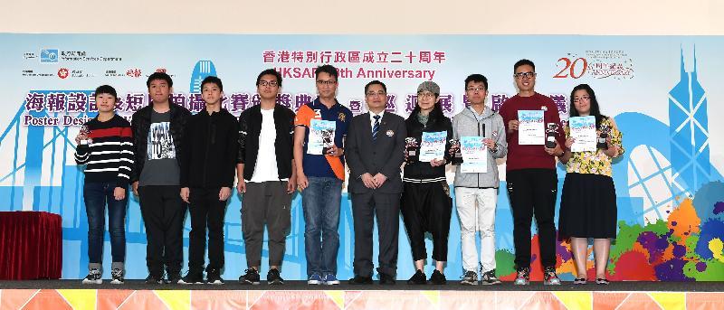 教育局首席教育主任吳加聲今日(四月十四日)頒發香港特別行政區成立二十周年海報設計及短片拍攝比賽的中、小學「最積極參與學校」獎,並與得獎學校代表合照。