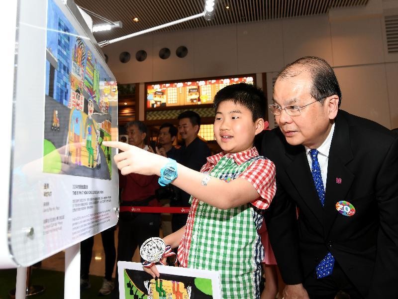 香港特別行政區成立二十周年海報設計比賽一名得奬小學生今日(四月十四日)與政務司司長張建宗分享創作理念。