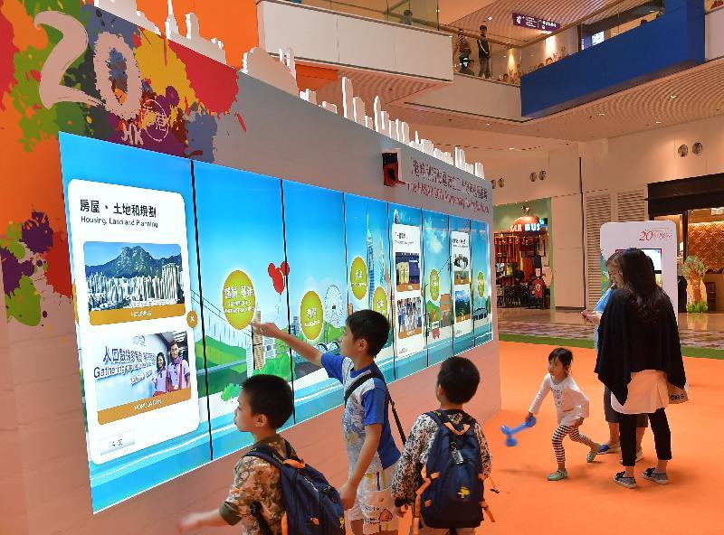 學生瀏覽巨型電子顯示屏幕上有關香港過去二十年發展和成就的照片。