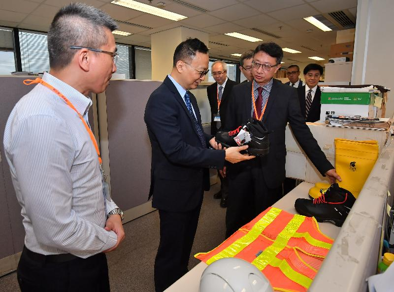 While visiting the Safety Promotion Unit of the Labour Department today (April 27), the Secretary for the Civil Service, Mr Clement Cheung (second left), is briefed by Occupational Safety Officers on the equipment they use for discharging their duties.