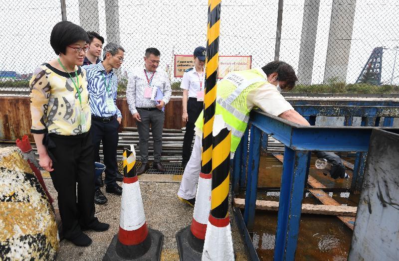 衞生署衞生防護中心聯同多個政府部門和機構今日(五月十二日)在香港葵涌八號貨櫃碼頭西(貨櫃碼頭)舉行代號「月光石」的演習,測試一旦出現寨卡病毒感染個案時相關政府部門和機構的應變能力。圖示衞生署署長陳漢儀醫生(左一)和衞生署衞生防護中心總監黃加慶醫生(左二)到貨櫃碼頭視察演習,食物環境衞生署人員在積水處進行滅蚊工作。