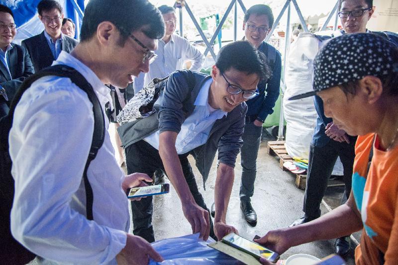 立法會議員朱凱廸(中)和何啟明(後排右二)今日(五月十五日)在香港中文大學觀看如何透過無線射頻識別電子標籤追蹤回收情況和記錄廢物量的示範。