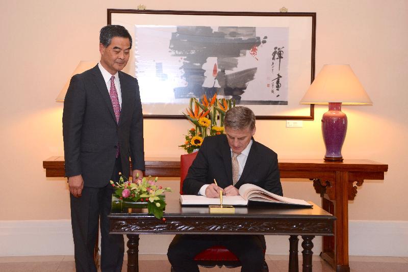 行政長官梁振英(左)今日(五月十九日)下午在禮賓府與訪港的新西蘭總理比爾.英格利希會面。圖示英格利希在禮賓府的貴賓冊上簽名留念。