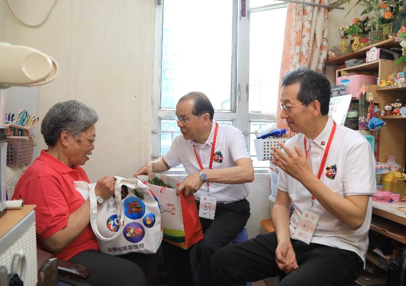 政務司司長張建宗(中)今日(五月二十日)在深水埗主持「共慶回歸顯關懷」計劃開展禮後到區內進行家訪,了解受訪家庭的生活情況和送上由行政長官梁振英親自種植的有機蔬菜,以及派發「二十周年慶祝活動禮物包」,與他們一同分享香港特別行政區成立二十周年的喜悅。