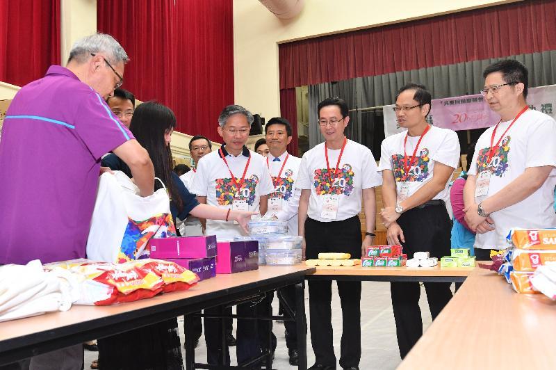 發展局局長馬紹祥(右三)今日(五月二十二日)到訪葵青區參與「共慶回歸顯關懷」計劃的家訪活動,義工在活動啟動禮上向參與家訪的官員示範包裝禮物包的程序。