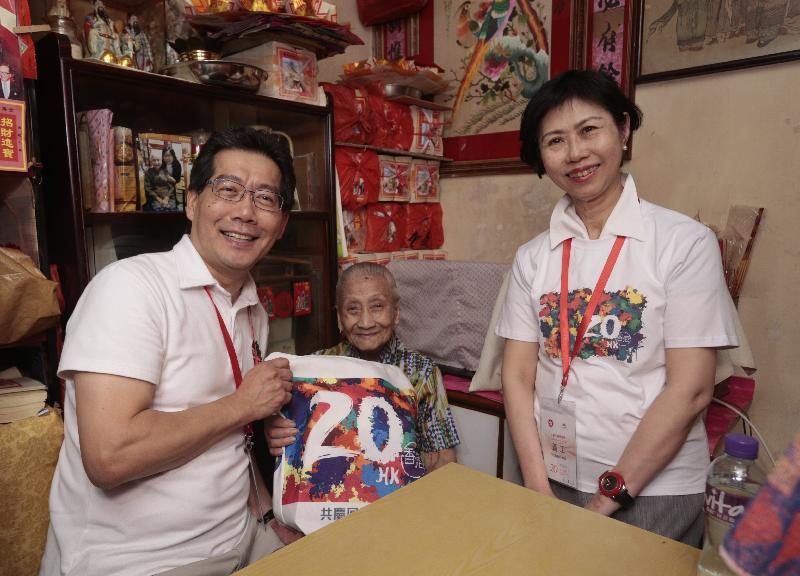 商務及經濟發展局局長蘇錦樑(左一)和香港聖公會福利協會總幹事李正儀博士(右一)今日(六月二日)到中西區探訪長者,並向她派發「二十周年慶祝活動禮物包」,共慶回歸。