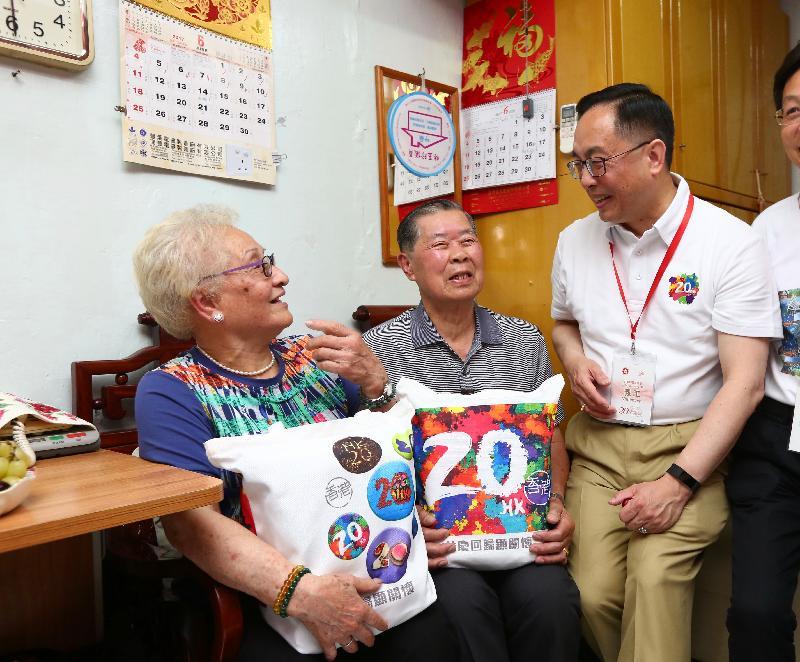 創新及科技局局長楊偉雄(右一)今日(六月十日)下午到鴨脷洲邨探望一戶長者夫婦,送上「二十周年慶祝活動禮物包」,共慶回歸。