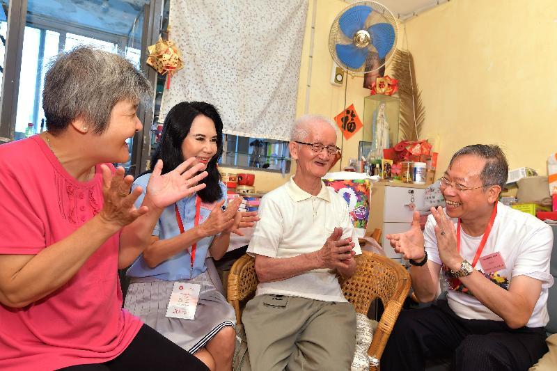 保安局局長黎棟國(右一)今日(六月十二日)探訪蝴蝶邨一個長者家庭,了解他們的生活狀況。