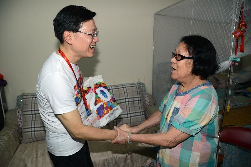 保安局副局長李家超(左)今日(六月十二日)到訪蝴蝶邨,向一個長者家庭派發禮物包。
