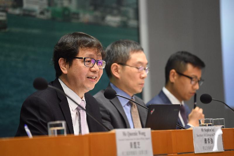 勞工及福利局局長蕭偉強(左)今日(六月十三日)出席有關工時政策整體框架的記者會,並簡介相關的建議及措施。圖示蕭偉強回應記者的提問。