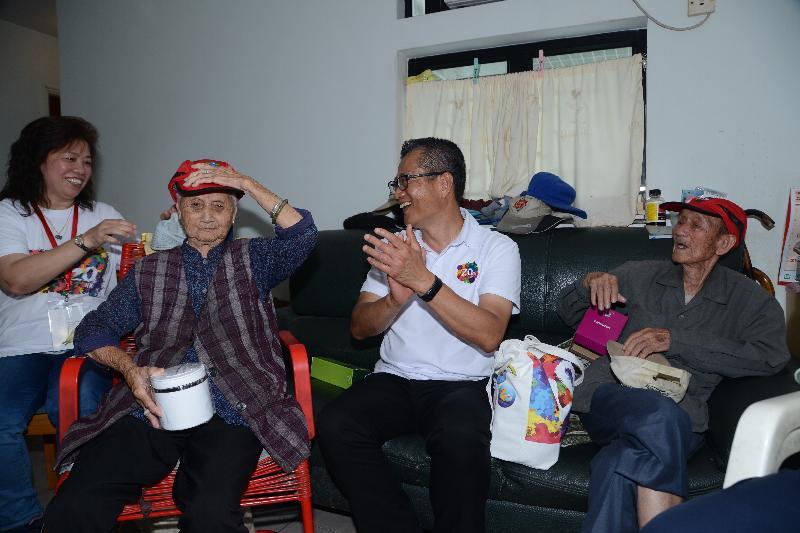 財政司司長陳茂波今日(六月十四日)參與「共慶回歸顯關懷」家訪活動,探訪西貢區的家庭。圖示陳茂波(中)了解受訪家庭的生活情況並派發「二十周年慶祝活動禮物包」,與他們一同分享香港特別行政區成立二十周年的喜悅。