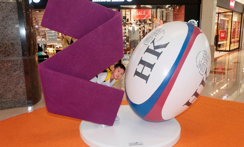「香港特別行政區成立二十周年巡迴展覽」今日(六月十六日)起在鑽石山荷里活廣場舉行。圖示小男孩與欖球立體模型拍照留念。