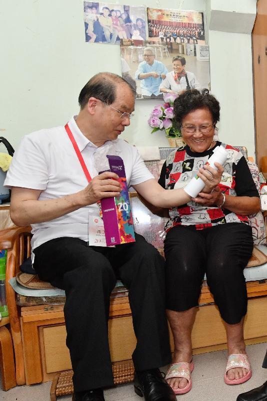 政務司司長張建宗今日(六月十六日)參與「共慶回歸顯關懷」家訪活動,探訪大埔區的家庭。圖示張建宗(左)向受訪家庭派發「二十周年慶祝活動禮物包」,分享香港特別行政區成立二十周年的喜悅。