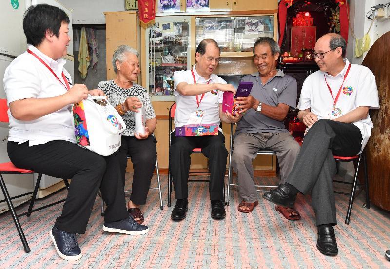 政務司司長張建宗今日(六月十六日)參與「共慶回歸顯關懷」家訪活動,探訪大埔區的家庭。圖示張建宗(中)向受訪家庭派發「二十周年慶祝活動禮物包」,與他們一同分享香港特別行政區成立二十周年的喜悅。