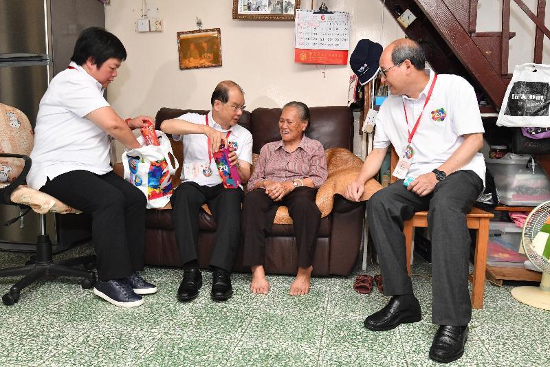 政務司司長張建宗今日(六月十六日)參與「共慶回歸顯關懷」家訪活動,探訪大埔區的家庭。圖示張建宗(左二)向受訪家庭派發「二十周年慶祝活動禮物包」,分享香港特別行政區成立二十周年的喜悅。