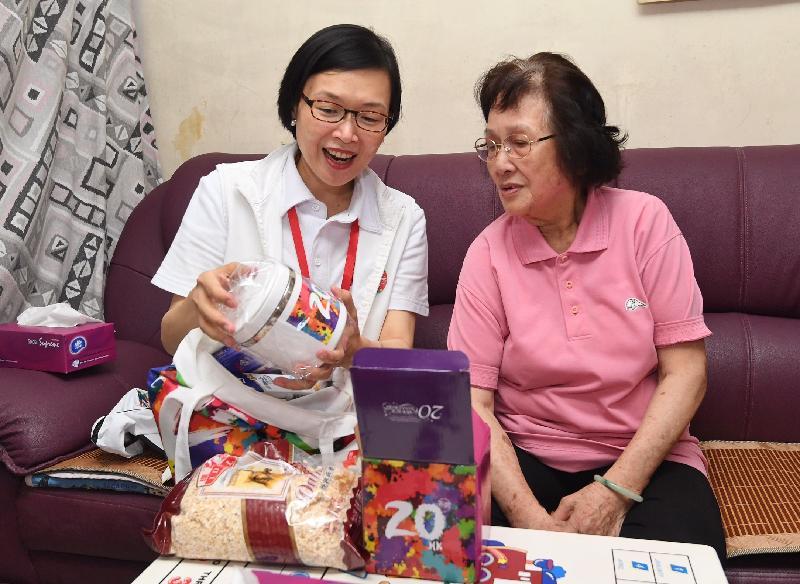 民政事務局副局長許曉暉(左)今日(六月十九日)探訪沙田新翠邨一位長者,了解其生活情況和派發禮品包。