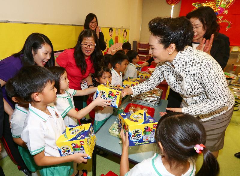 國家主席習近平夫人彭麗媛(右)今日(六月二十九日)參觀又一村學校時,送贈繪畫水筆給學生,並向幼稚園贈送多部多媒體教學機。