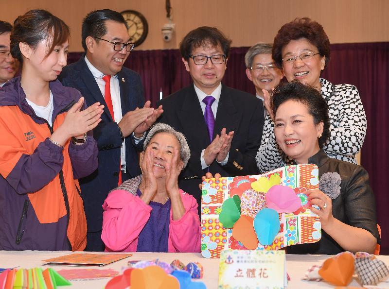 國家主席習近平夫人彭麗媛(前排右)今早(六月三十日)到訪在黃竹坑的東華三院賽馬會松朗安老綜合中心,對一位製作立體卡的長者表示讚賞。陪同她探訪的包括中央人民政府駐香港特別行政區聯絡辦公室副主任殷曉靜(第二排右一)、勞工及福利局局長蕭偉強(第二排右二)和東華三院主席李鋈麟(第二排左二)。