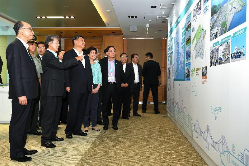 國家主席習近平(左三)今日(七月一日)在機場行政大樓觀看展板,並聆聽香港機場管理局主席蘇澤光(左二)介紹香港國際機場在配合粵港澳大灣區發展擔當的角色。行政長官林鄭月娥(左四)、運輸及房屋局局長陳帆(左一)和香港機場管理局行政總裁林天福(左五)在場陪同。
