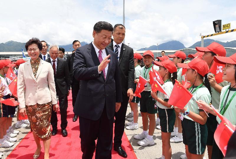 國家主席習近平(中)今日(七月一日)離港前在機場向送行的小童揮手道別。行政長官林鄭月娥(左一)及丈夫林兆波(左二)亦有送行。