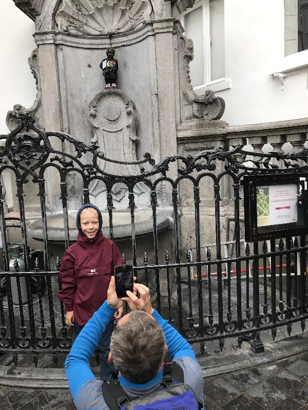 父親為小男孩在世界著名的噴泉雕像兼布魯塞爾的珍貴市標前拍照。