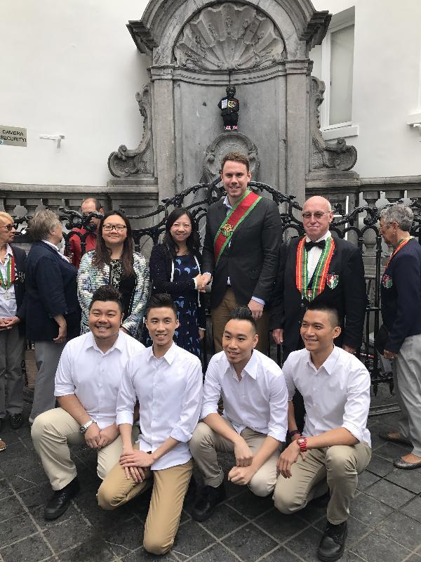 香港駐歐洲聯盟特派代表林雪麗(左二),與香港首個專業無伴奏合唱團「一舖清唱」(前排)合照,並與布魯塞爾市議會代表(右二)握手。同場為香港駐布魯塞爾經濟貿易辦事處副代表蔡敏君(左一)和「撒尿小孩銅像之友會」代表(右一)。