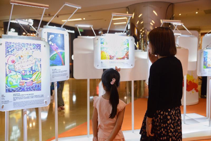 「香港特別行政區成立二十周年巡迴展覽」今日(七月十五日)起在太古城中心舉行。圖示參觀展覽的市民欣賞特區成立二十周年海報設計比賽的得奬作品。