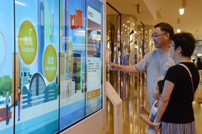「香港特別行政區成立二十周年巡迴展覽」今日(七月十五日)起在太古城中心舉行。圖示參觀展覽的市民通過電子觸控式屏幕,回顧香港過去二十年的發展和成就。