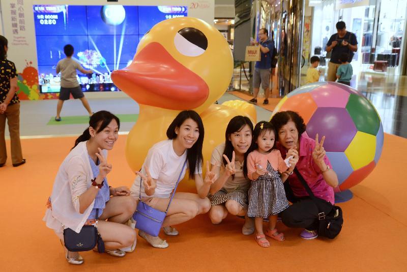 「香港特別行政區成立二十周年巡迴展覽」今日(七月十五日)起在太古城中心舉行。圖示參觀展覽的家庭與小黃鴨和足球立體模型拍照留念。