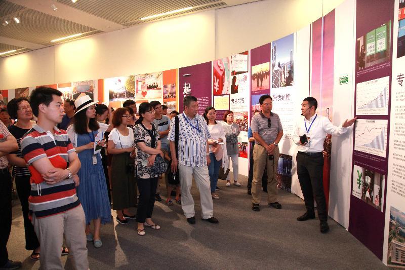 由香港特別行政區政府在北京中國國家博物館舉辦的「香港回歸祖國二十周年——同心創前路 掌握新機遇」成就展於今日(七月十六日)圓滿結束。圖示參觀者細心聆聽工作人員的講解。