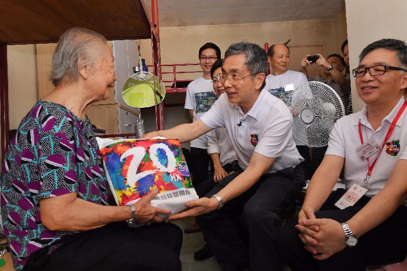 財經事務及庫務局局長劉怡翔(中)今日(七月十九日)上午參與南區「共慶回歸顯關懷」家訪活動,向一名石排灣邨的長者送上禮物包。